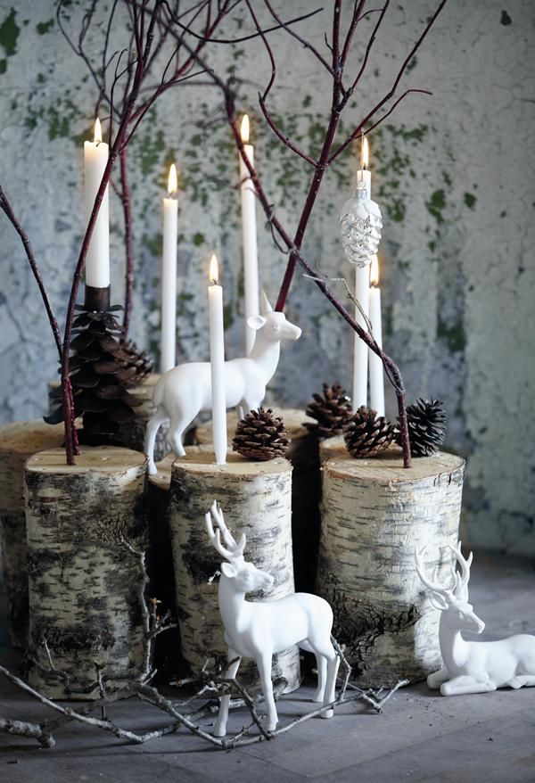 white reindeer on birch logs with white candles centerpiece for Christmas