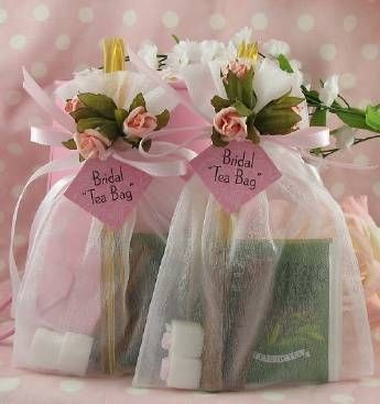 5 X 7 inch white organza bag tied with pink satin ribbon and three blush pink roses. Inside are 2 herbal tea blends, 2 lemon-infused honey sticks, 2 cinnamon sticks and 2 rose-topped sugar cubes
