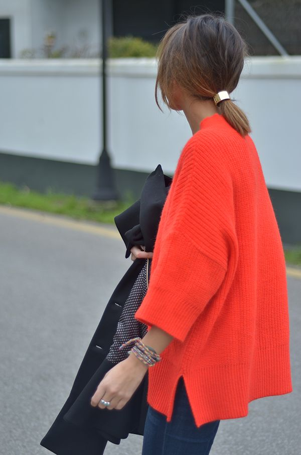 Love the slouchiness of the coral poncho sweater with the structure of that glossy gold ponytail ring.