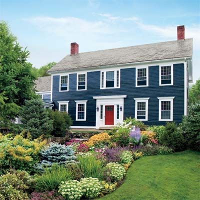 Beautiful blue colonial style house with impeccable gardens along the walkway and a perfectly manicured lawn. The white trim around the windows and the bright red door give this house such character!