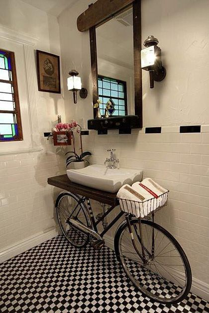 bathroom vanity. The bicycle's handlebar basket was cleverly designed to hold towels right next to the sink. The entire bathroom was designed by Bullins, is currently for sale and includes a mirror made from a trombone case and light fixtures made from coach lights.
