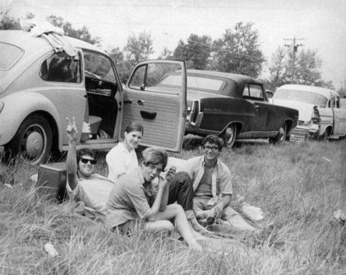 Roadtrip roadside picnic. Cars on side of road. People eating in the grass.