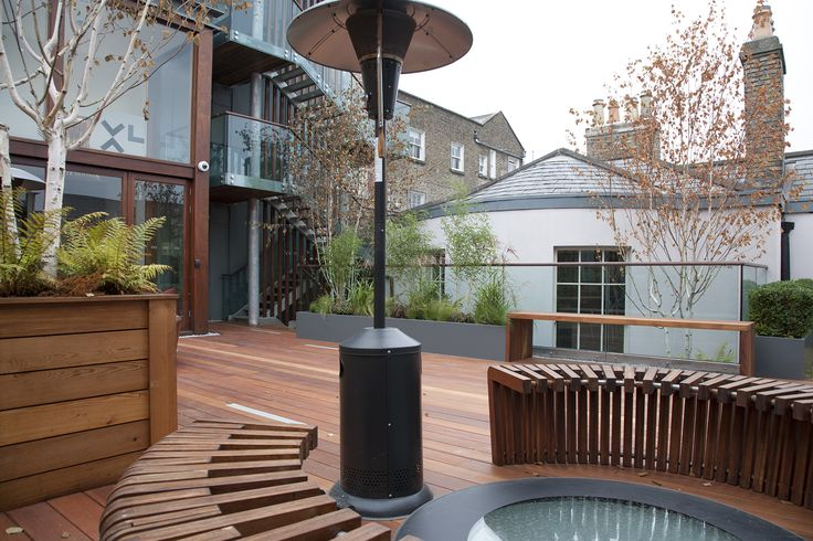This roof garden was built at the back of a Georgian house for its staff and visitors. Hardwood decking and wall cladding planted with evergreen climbers, raised planters  filled with trees and shrubs surround this contemporary design, maximising the potential of the space available