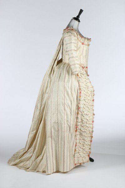 A rare brocaded silk robe à la Piémontaise, 1770s, the silk woven with delicate foliate stripes, the bodice with tabbed front hem, trimmed in tufted pink, brown, green and gold fly braid, with padded, ruched bands to the front skirt openings, pleated drape falling desending over the fourreau back and culminating in polonaised skirt drapes, two silk covered buttons to the rear waist