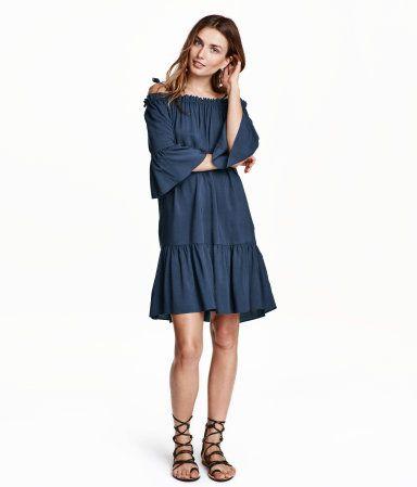 Knielanges, schulterfreies Kleid aus Viskosestoff. Modell mit 3/4-langen Ärmeln und schmalen, verstellbaren Trägern. Gummizug und schmaler Volant am oberen Abschluss. Breiter Volant an Ärmeln und Saum. Ungefüttert.