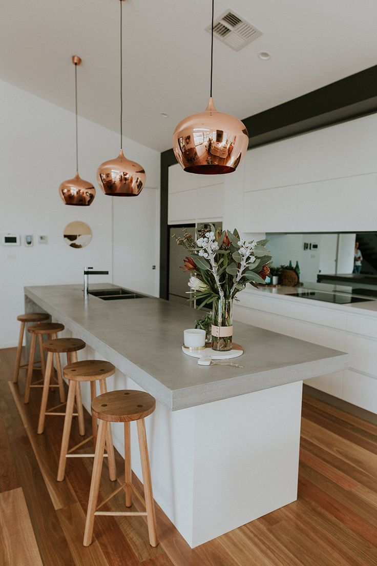 Chifley house in Canberra, Australia designed by Studio Black Interiors. This modern kitchen is contemporary but full of warmth and elegance. The concrete benchtop paired with the warmth of the copper pendants, timber stools and chrome and black sink mixer creates a modern, stylish look.