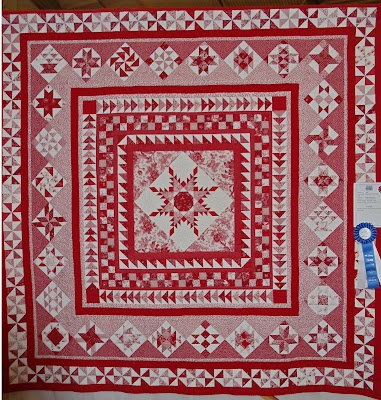 Red and white medallion quilt that won a blue ribbon...love it. Feathered star, sawtooth border, sampler blocks and pinwheels.