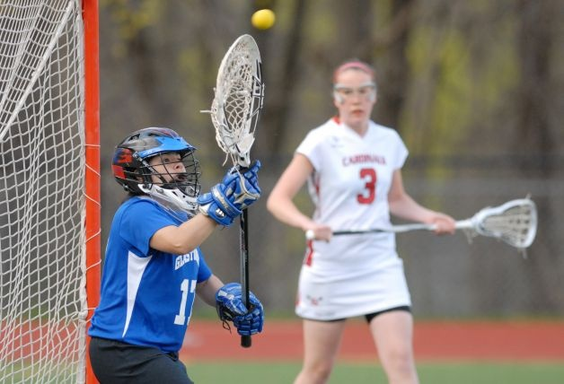 Glastonbury High School lacrosse goalie Marina Molnar during the girls high school lacrosse match between Greenwich High School and Glastonbury High School at Greenwich, Tuesday April 10, 2012. Greenwich won the match 19-9. At right is Claire feeney of GReenwich who scored seven goals during the game. Photo: Bob Luckey  Read more: http://www.greenwichtime.com/sports/article/Feeney-scores-seven-goals-as-Greenwich-girls-3472892.php#ixzz2RZh1JOPu