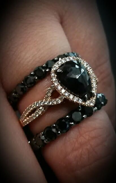 A single rose cut   pear shape black diamond weighing 1.52 carat sits surrounded by a halo of 86 sparkling white diamonds totaling 0.34ctw in this unique 14k rose gold black diamond ring. This captivating ring is handcrafted to enhance each black diamond center stone and available from Coby Madison Jewelry.