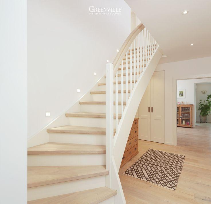 Ein eleganter und ordentlicher Flur mit weißer Treppe, hellem Boden und einem d