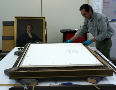 "Rick Meyers, Exhibits Preparator, works on a painting titled Gratiot Street Prison, on display in The Civil War in Missouri exhibit. The simplest way to begin the stabilization of paintings or other types of framed artwork is to provide protective layers in the front and back. The front protective layer is referred to as ""glazing,"" which ideally would be a type of Plexiglas that is UV filtering, anti-reflective, and anti-static.: Civil War"