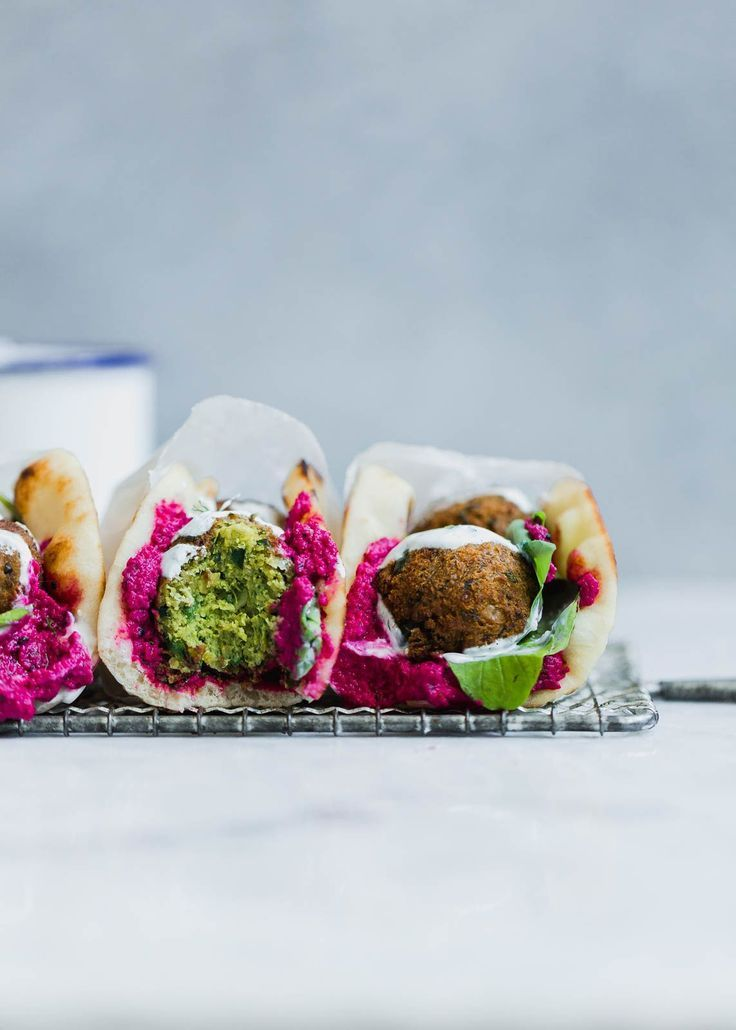 Homemade green falafel filled with spinach and garden herbs, smothered between b…