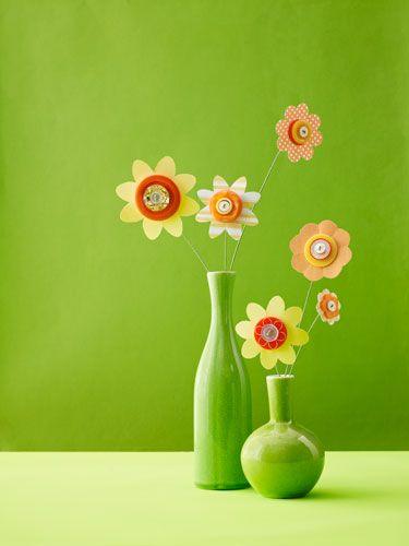 Turn scrap paper and extra buttons into quirky, colorful flowers, which you can turn into wall art, displays, journals and more! Flip through to learn how to make the flowers. MATERIALS · Scrapbook paper · Scissors · 3 buttons per flower: 1 large, 2 small · Pencil · Precut floral stem wire · Wire cutters