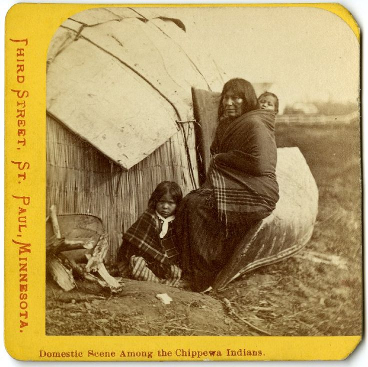 A Chippewa woman carrying a baby on her back, sitting on an upturned canoe,