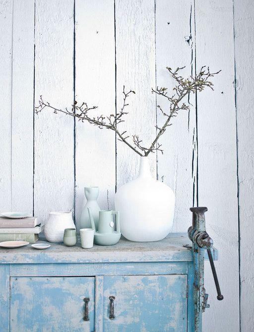 Poederig getinte porseleinen vazen, op een ijsblauw ruig industrieel kastje, tegen een 'sloophouten' wand.