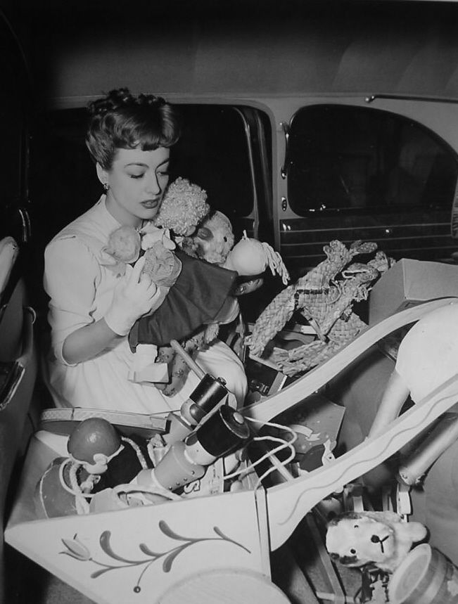 Joan Crawford arrives with a car load of toys at a nursery she helped set up -1943