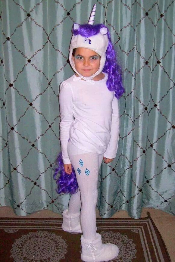 My little pony Rarity costume.  Purple wig cut in half sewn on to white tights and white hat. Tutorial on YouTube on how to make unicorn horn and ears out of felt. Printed a picture of Rarity on picture paper and glued it on the hat. Diamonds were drawn on with blue glitter puff paint.