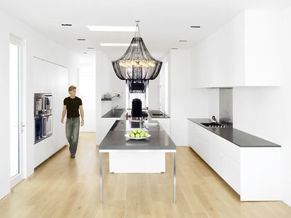MinimalistKey elements: The statement chandelier creates a large focal point over the futuristic stainless steel island. The cabinets practically recede into the walls visually, and skylights make things even brighter.