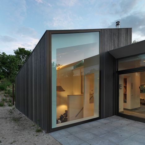 Larch-clad holiday home by De Zwarte Hond huddles behind the dunes on a Dutch island