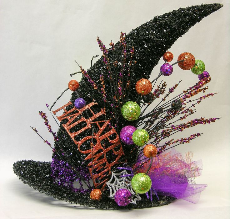 """A black 12"""" witch glittered hat with a """"Happy Halloween"""" sign, glittered stems and puffs of tulle ribbon. A 6"""" X 4"""" X 3"""" green/black glittered spider is perched on the back. Just the right size to acc"""