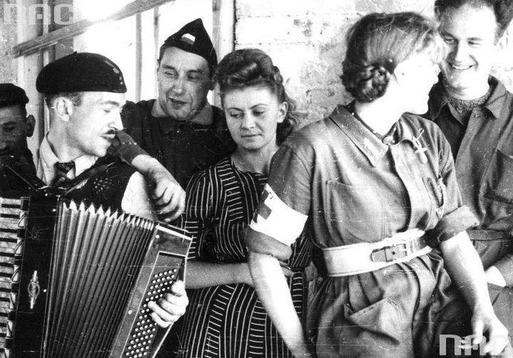 """Group of insurgents in the villa Brodziszów in Mokotów, ul. Malczewski. Visible from left: Waclaw Żdżarski (playing the accordion), Sec. """"Krzysztof"""" John Markowski, nurse """"Małgorzatka"""" Janina Załęska."""