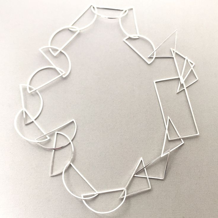 Sterling silver statement necklace made from interlocking semi circles, triangles and a large rectangle.  Approximately 70cm in length, the necklace fits comfortably over the head without the need for a clasp.