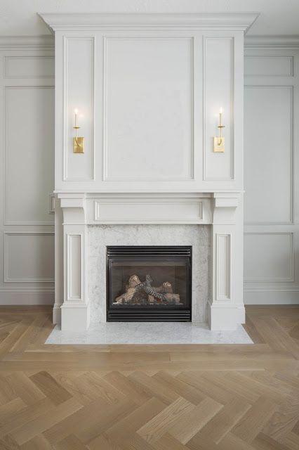visual comfort sconces, gray wainscot room, herringbone floors, carrara marble fireplace surround via WHITE + GOLD