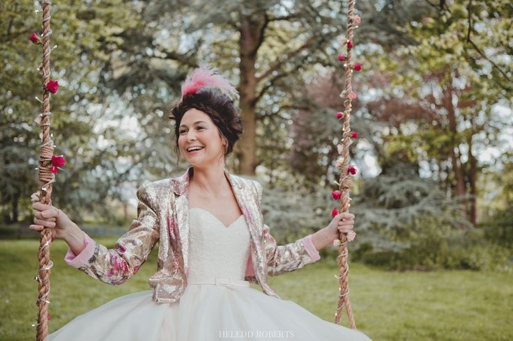 A smiling bride sat on a wedding tree swings with rope dressed with flowers, a magical addition to your wedding photographs