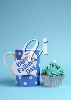 Happy Fathers Day special treat blue and white beautiful decorated cupcakes with message on blue background, with blue polka dot coffee mug. Vertical with copy space for your text here.