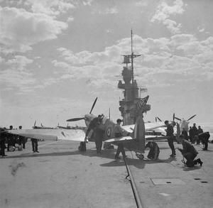 "SPITFIRES FOR MALTA. 19 TO 23 MARCH 1942, ON BOARD HMS EAGLE. HMS EAGLE IN COMPANY WITH ""FORCE H"" TAKING SPITFIRES FROM GIBRALTAR TO MALTA FOR THE DEFENCE OF THE ISLAND. THE AIRCRAFT WERE FLOWN OFF HMS EAGLE AFTER BEING TAKEN HALF WAY ON BOARD THE CARRIER. (A 9580)"