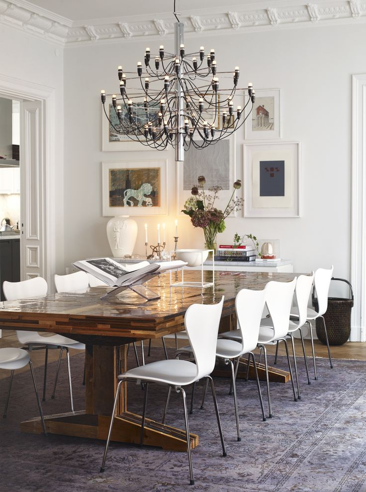 Piet Hein Eeks table, made from waste wood, specially ordered from NK. Around the table are ten Seven Chairs by Arne Jacobsen. The large antique carpet from Knut is bleached and colored in gray. Ceiling light units in 2097, designed by Gino Sarfatti for Flos.