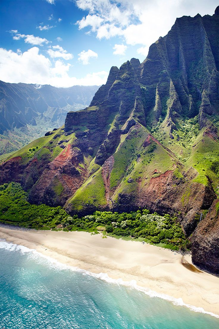 The Hawaian island of Kaua'i - more specifically, the isolated Kalalau Beach (with its namesake valley just behind), which is the terminus of the notoriously tough Kalalau Trail, which runs along the Na Pali coast.