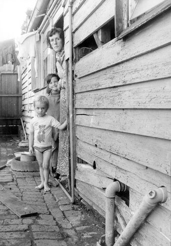 April 1977:  Melbourne resident Elizabeth Thompson stands with her two children, Paul and Jane, in their house in Thompson St, Kensington. The house was described by the Tenants' Union as one of the worst ever seen. - Melbourne's slums | City's slum heritage | Photo Galleries and News Photos | News Pictures and Photos | Herald Sun