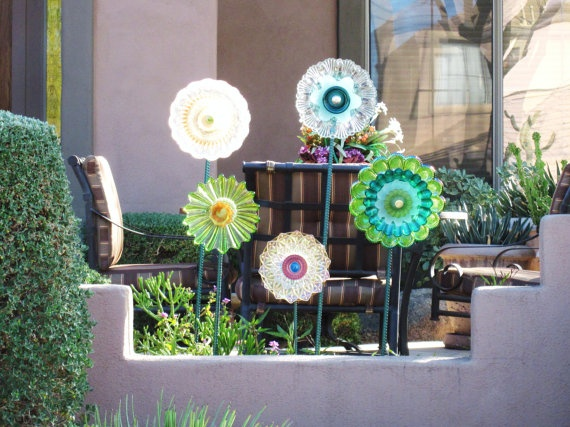these glass flowers are made from antique plates and dishes glued together.