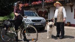 Eva steht mit ihrem Fahrrad vor dem Fallerhof, daneben Hermann mit Willy, der einen Maulkorb trägt, Quelle: SWR/Christina Appel