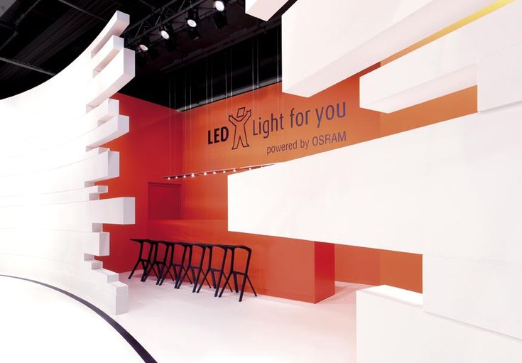 A very clean stand for Osram - A bright white wall which opens out into a vivid orange booth.  #eventprofs #entranceideas
