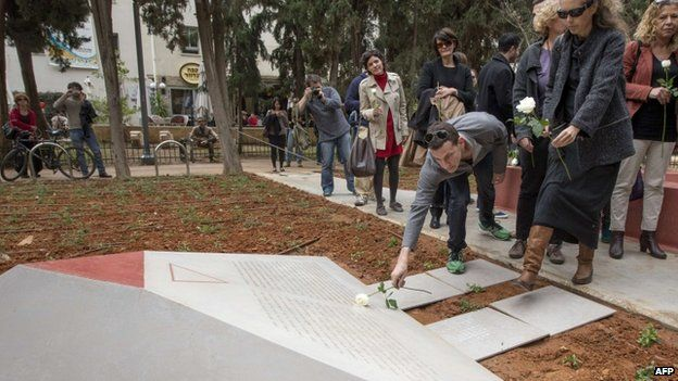 People lay flowers at a memorial to thousands of gay Holocaust victims killed by the Nazi during the Second War at the Gan Meir (Meir Park) during its inauguration on January 10, 2014 in the Mediterranean coastal city of Tel Aviv