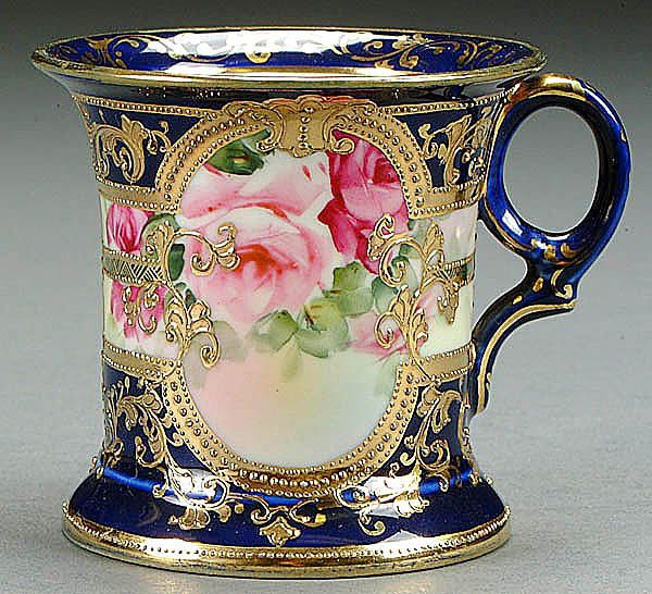 : A NIPPON COBALT DECORATED SHAVING MUG CIRCA 1900 WITH HAND PAINTED ROSES IN GILT CARTOUCHE.