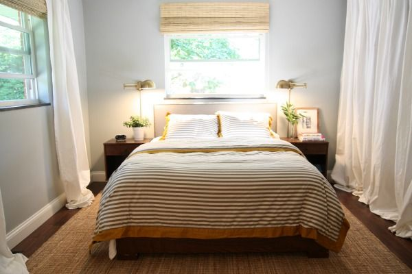 Gray walls, low bed under window, antique brass sconces, nightstands from Overstock, window shade from Overstock