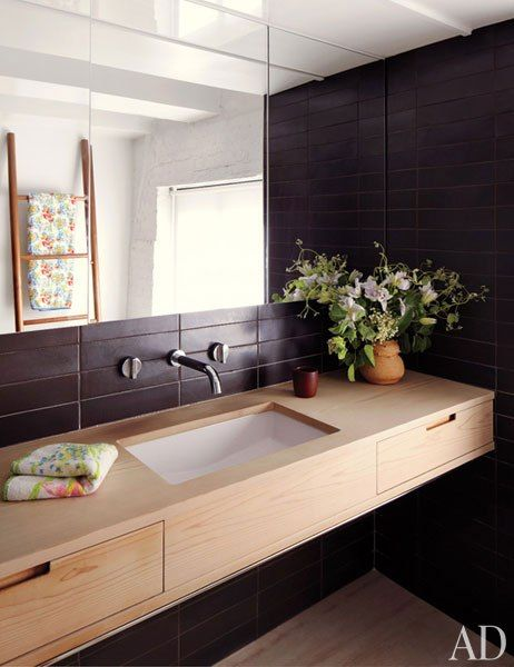 The master bathroom's custom-made vanity is red cedar, the tile is by Heath Ceramics, and the fittings are by Boffi.