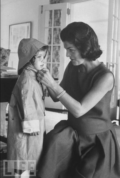 vanemuse:  Jacqueline and Caroline KennedyJackie helps Caroline put on her rain hat and slicker before going out to play, in 1960.
