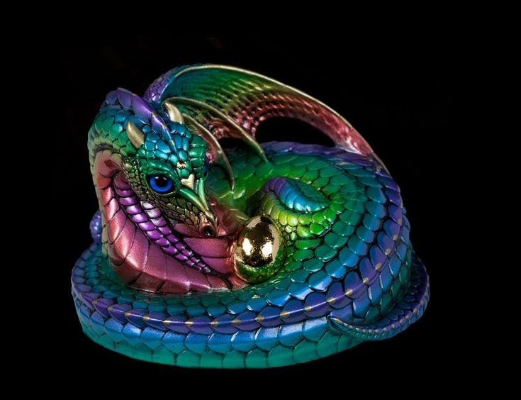 This Mother Coiled Dragon is painted to match our retired family of Rainbow colored dragons. She has dark blue glass eyes and a topaz colored Swarovski jewel in her forehead. She coils protective…