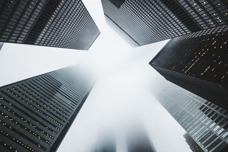 A low-angle shot of dark skyscrapers on a foggy day