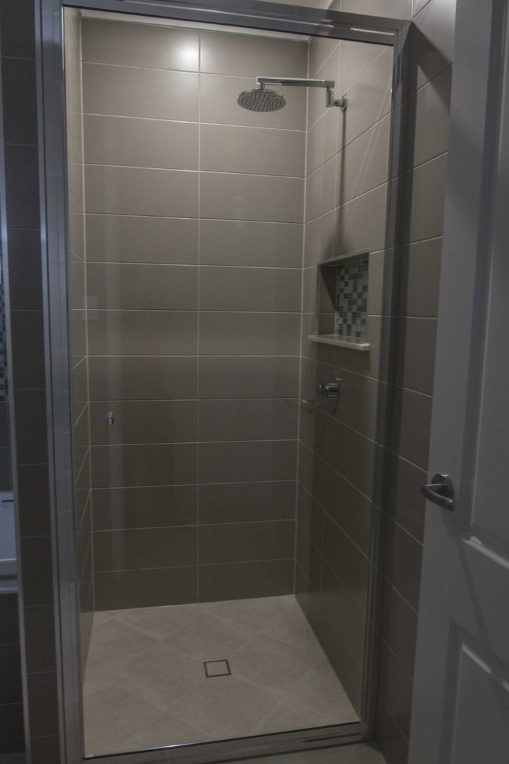 Moody brown bathroom shower with overhead light - built by Grady Homes in Townsville, Australia