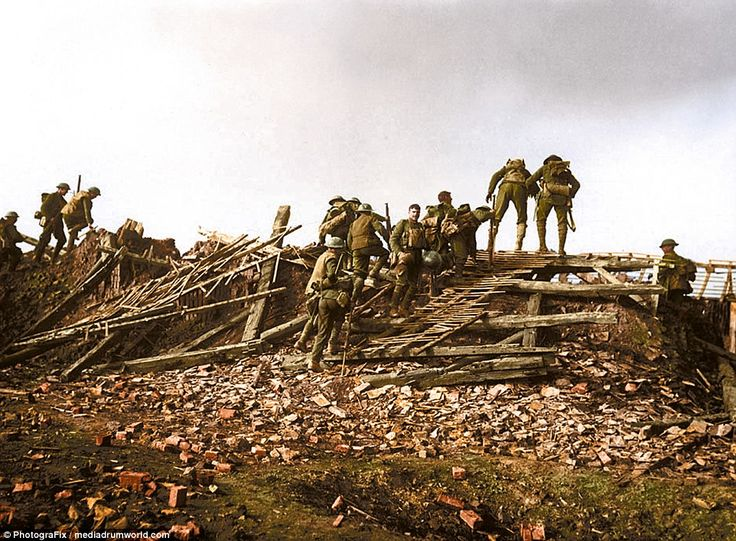 Carrying heavy packs and metal helmets, a group of British soldiers continue their journey across a landscape littered with  debris