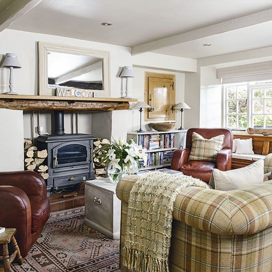 Traditional living room with tweed sofa, cosy country cottage in the Lake District. Almost every item in the cottage has been unearthed from a fair or second-hand shop and then modified, colour-washed or reupholstered. The window seat was created out of a discarded church pew, while an old Chesterfield sofa was brought up to date with a trendy tweed covering.