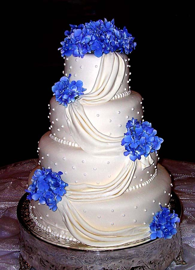 White Bridal Bouquets with a Touch of Blue | Four tier white wedding cake with white satin ribbon and hydrangeas.