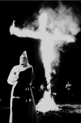 KKK member pictured in front of the klan symbol of a burning cross