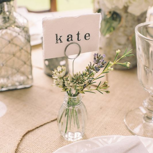 Doubling as vases for white carnations, simple wedding place cards are tucked into clear glass holders.
