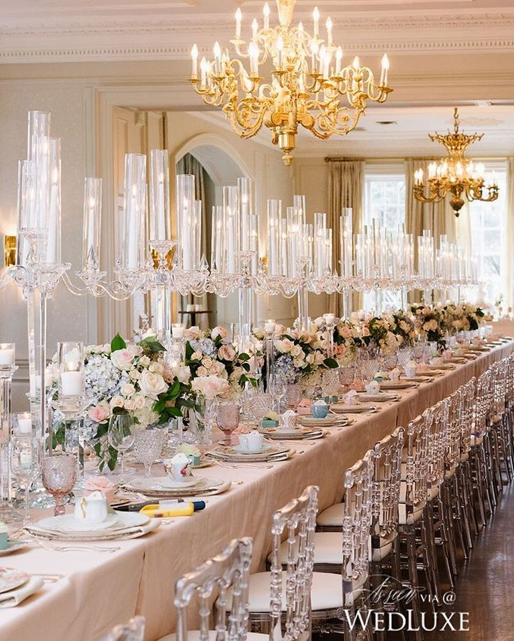 Decorated in crystal candelabras and lush floral #centrepieces, the glittering, romantic runner effect is simply breathtaking! | Photography By: Mango Studios | WedLuxe Magazine | #wedding #luxury #weddinginspiration #luxurywedding #reception #tablescape #chandelier #tablesetting